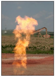 A flare burning natural gas glimmers in front of a pumping unit north of New Town.