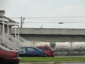 Photo:  Front porches in Mobile's Orange Grove Homes housing development, with trains in the background. (Photo credit Karen Savage)
