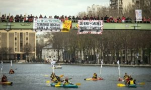 Indigenous people paddle down the Seine as others stand on a bridge holding banners during a rally in Paris demanding Indigenous rights are included in the climate accord on December 6, 2015 on the sidelines of the COP21 climate change conference. / AFP / LIONEL BONAVENTURELIONEL BONAVENTURE/AFP/Getty Images Photograph: Lionel Bonaventure/AFP/Getty Images